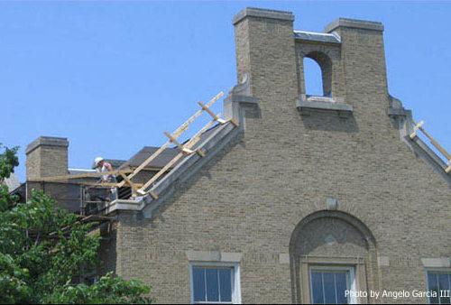 Un hombre arregla el tejado de un edificio