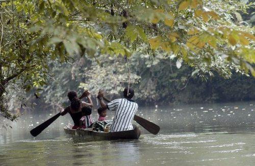 Una familia en una barca de remos navegan por el río